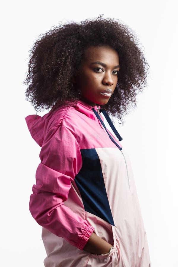 La jeune fille châtain bouclée hardie habillée dans la veste de sport rose se tient au fond blanc dans le studio photos libres de droits