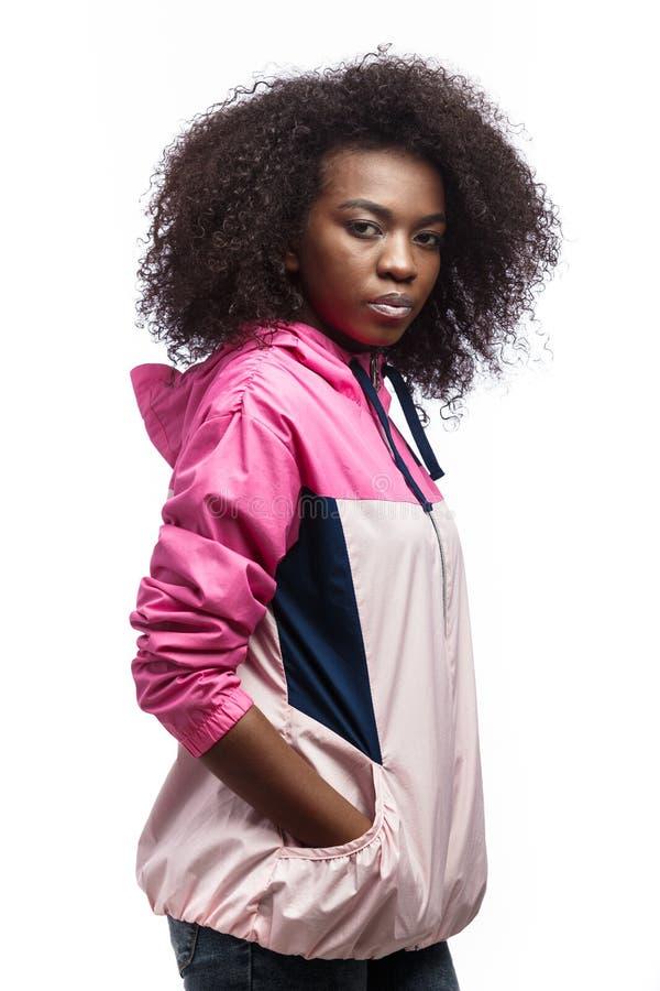 La jeune fille ch?tain boucl?e hardie habill?e dans la veste de sport rose se tient au fond blanc dans le studio photos libres de droits