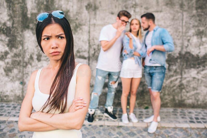 La jeune fille chinoise bouleversée se tient devant la photo et regarde au theside Elle a croisé ses mains Ses amis images stock