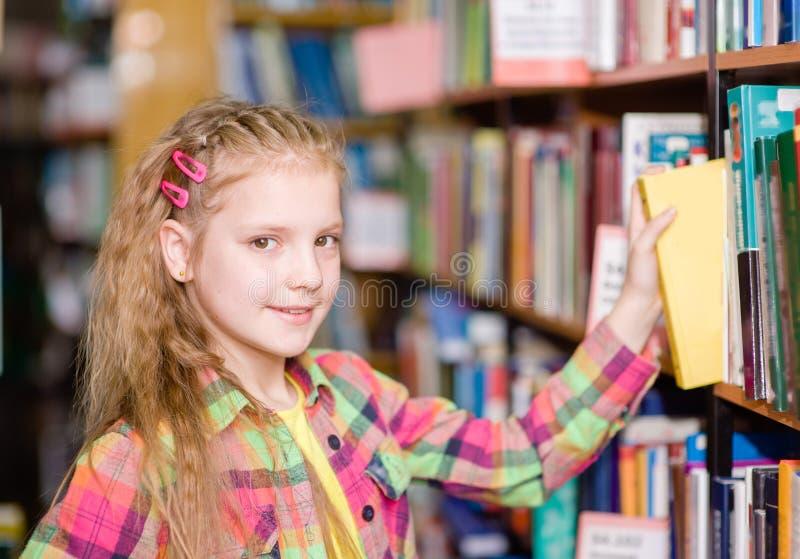 la jeune fille choisit un livre dans la bibliothèque images stock