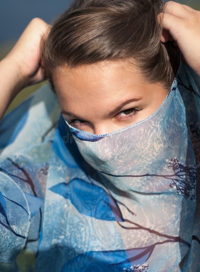 La jeune fille a couvert son visage d'écharpe bleue photo libre de droits