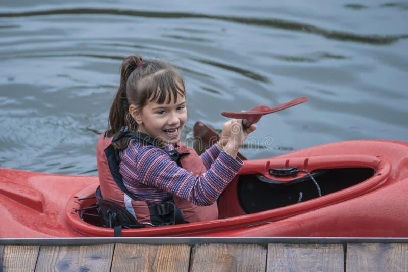 La jeune fille d'adolescent contrôle activement un bateau de kayak de sports sur un être photo stock