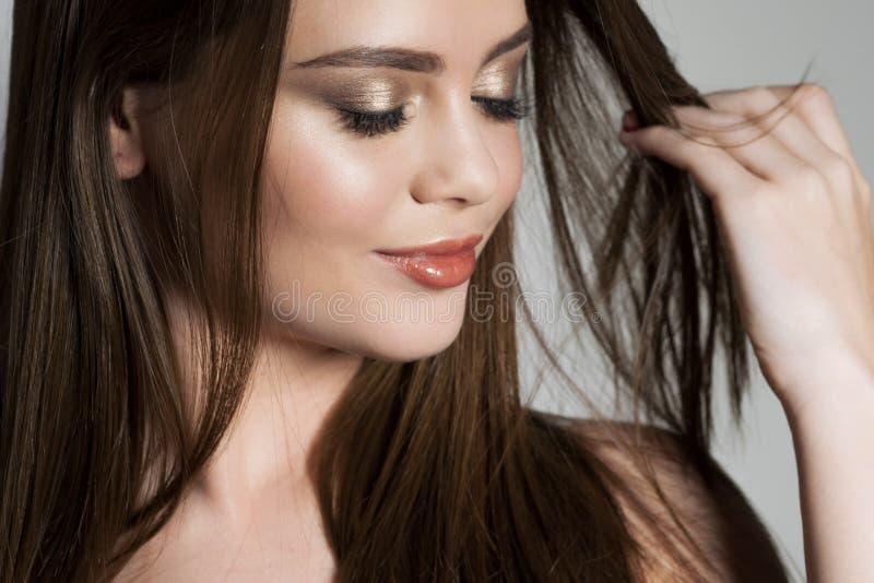 La jeune fille d'une chevelure brune attirante touche ses cheveux sains et soyeux photo stock