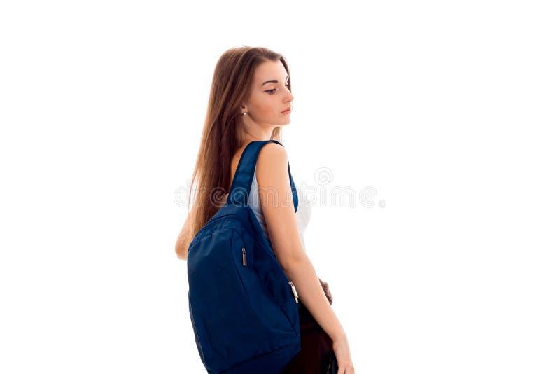 La jeune fille dans la chemise blanche et avec un portfolio a tourné le sien de nouveau à l'appareil-photo photos libres de droits