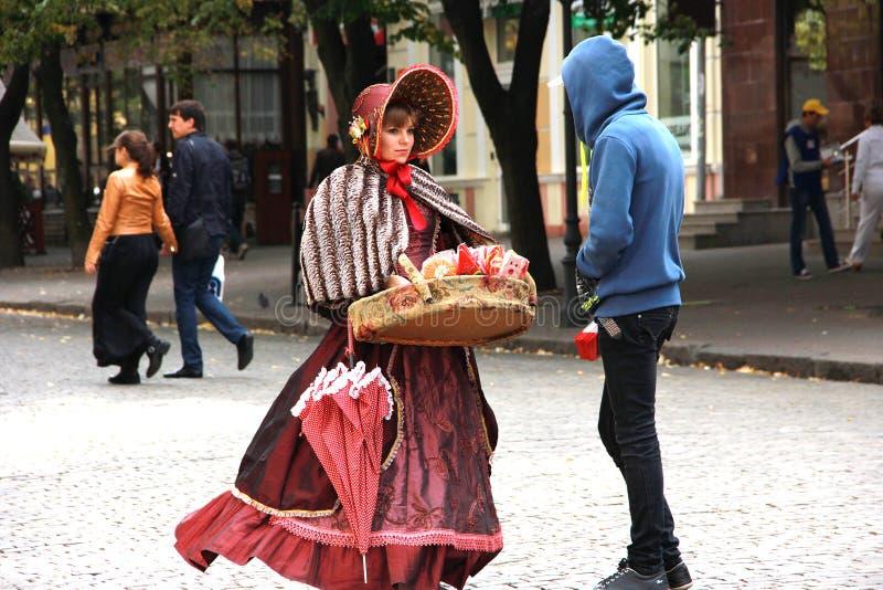 La jeune fille dans la robe démodée vend la sucrerie du plateau image stock