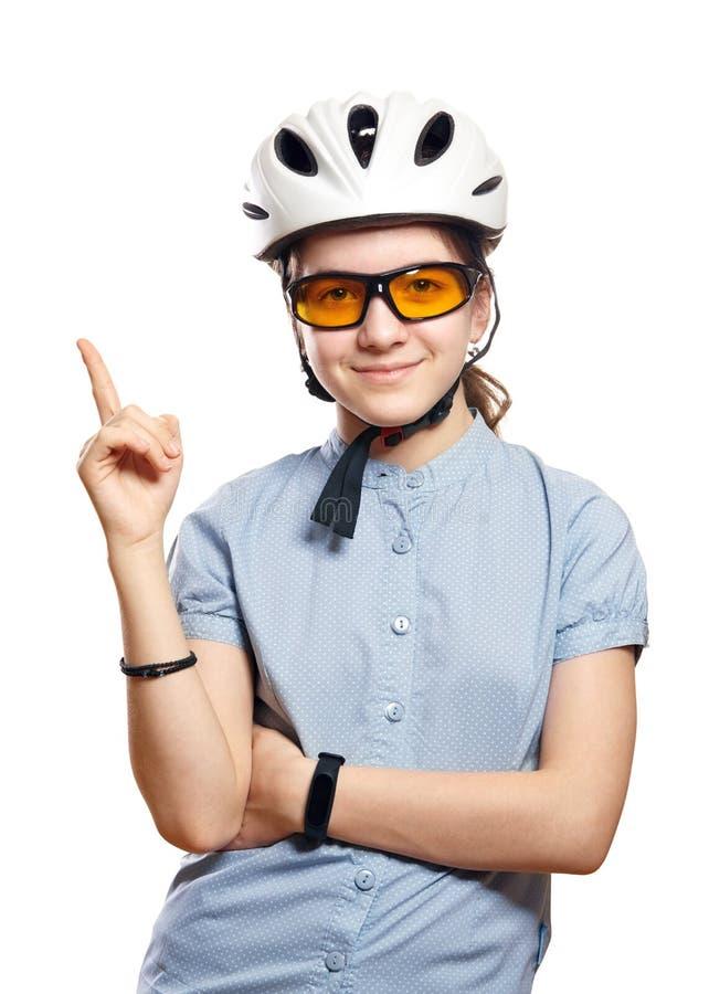 La jeune fille dans le casque de bicyclette indique l'espace, isolement sur le blanc photographie stock libre de droits