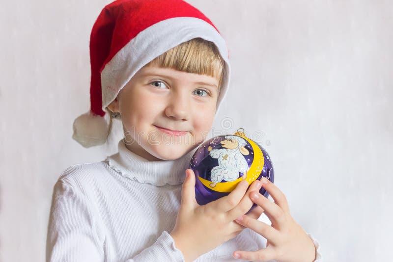 La jeune fille dans le chapeau Santa Claus sur un fond blanc tient la boule de Noël Portrait d'un enfant photographie stock libre de droits