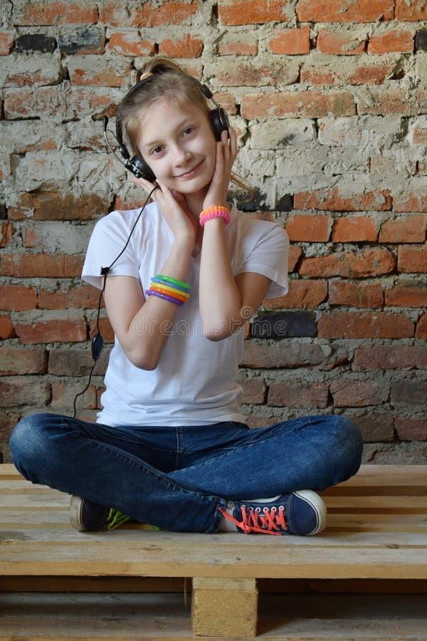 La jeune fille dans les jeans et le T-shirt blanc s'assied sur le plancher et ?coute la musique par des ?couteurs Portrait de con photographie stock libre de droits