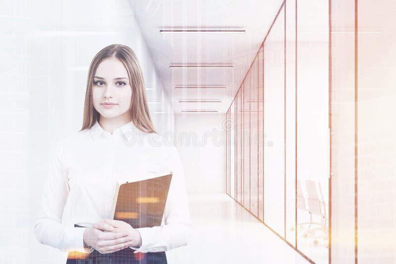 La jeune fille dans un costume de bureau tient un dossier et une position noirs dans un couloir blanc de bureau avec des salles d illustration libre de droits
