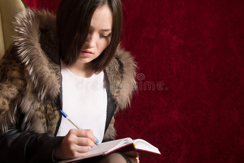 La jeune fille dans un manteau de fourrure s'assied de retour et prend des notes photo stock