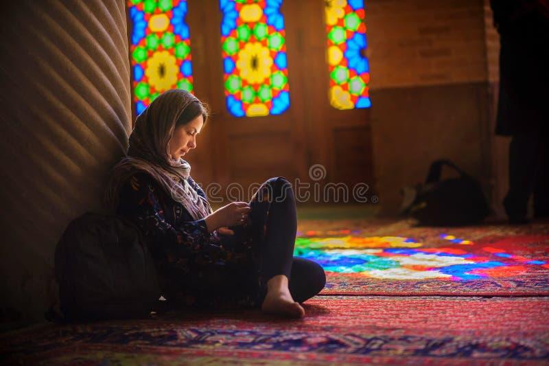 La jeune fille dans une écharpe s'assied sur un plancher dans la mosquée photo libre de droits