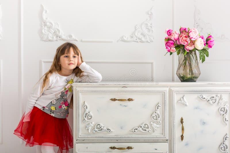 La jeune fille dans une jupe rouge s'est penchée sur la raboteuse Sur la raboteuse est un bouquet des tulipes photo libre de droits