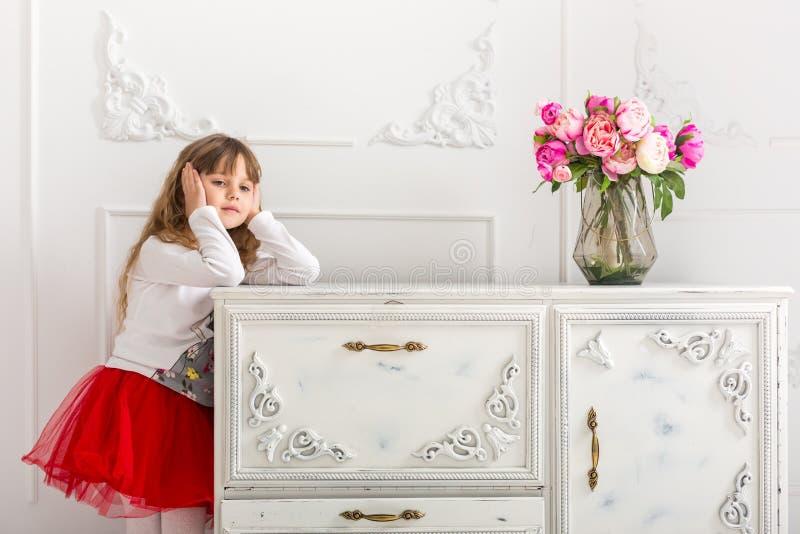 La jeune fille dans une jupe rouge s'est penchée sur la raboteuse Sur la raboteuse est un bouquet des tulipes image libre de droits