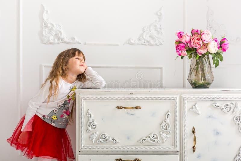 La jeune fille dans une jupe rouge s'est penchée sur la raboteuse Sur la raboteuse est un bouquet des tulipes images libres de droits