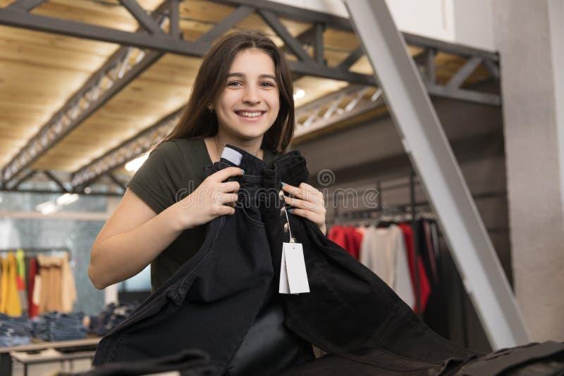 La jeune fille de brune choisit ses jeans dans le magasin photo stock