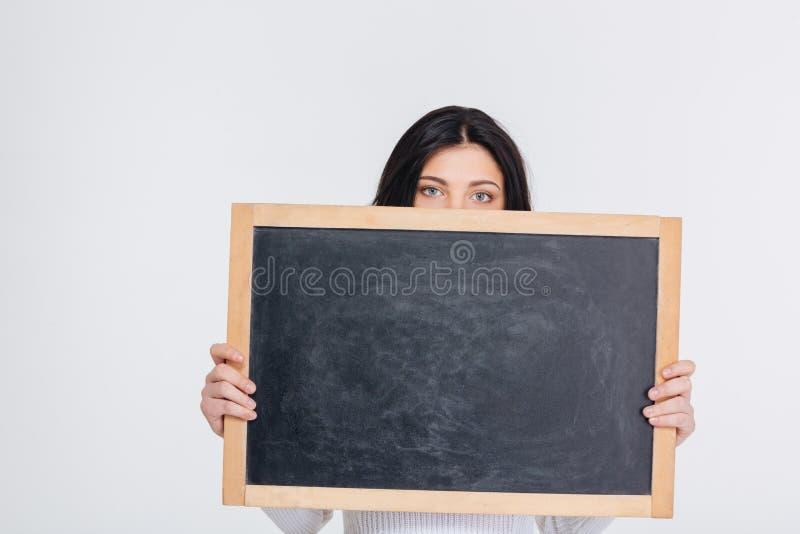 La jeune fille de brune couvre son visage de tableau vide photo stock