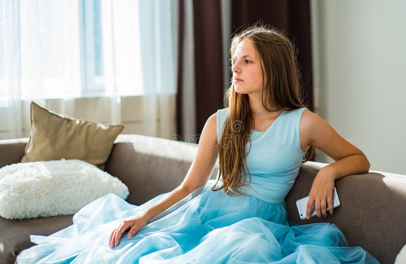 La jeune fille de brune d'adolescent avec de longs cheveux se reposant sur le sofa ont à la maison l'amusement utilisant le smart photo stock