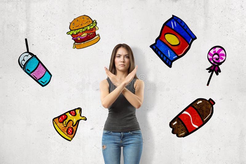 La jeune fille de brune portant les jeans occasionnels et la représentation de T-shirt refusent le signe aux casse-croûte malsain photographie stock libre de droits