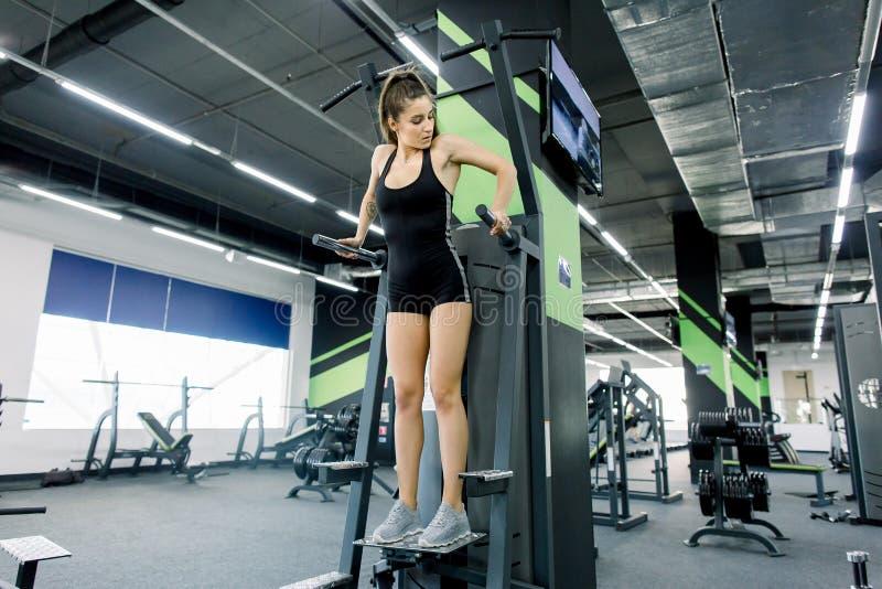 La jeune fille de forme physique tire vers le haut dans le gymnase Femme de forme physique de brune dans l'usage noir de sport av photos stock