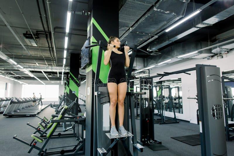 La jeune fille de forme physique tire vers le haut dans le gymnase Femme de forme physique de brune dans l'usage noir de sport av photo stock