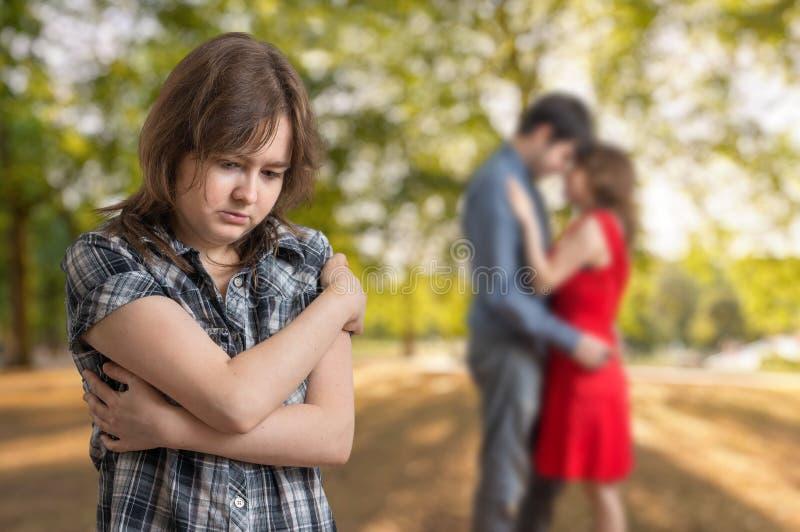 La jeune fille de jalousie voit son ami avec une autre fille images stock