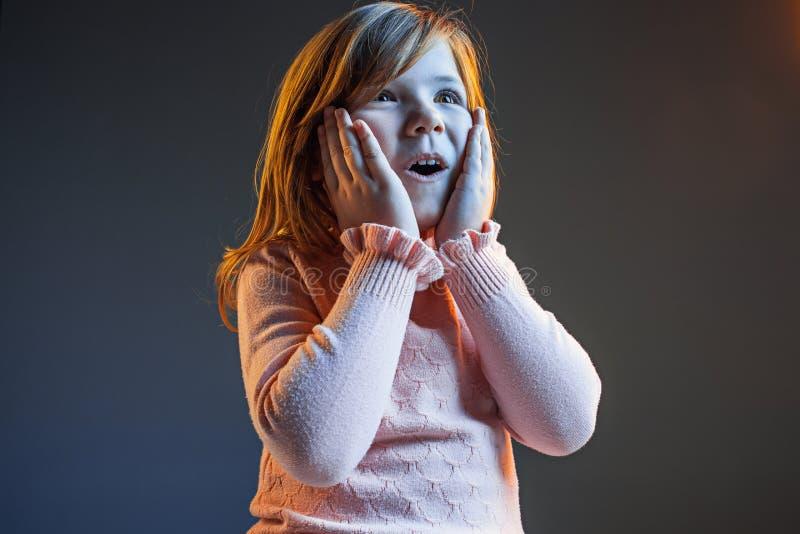 La jeune fille de l'adolescence attirante semblant étonnée sur bleu-foncé image stock