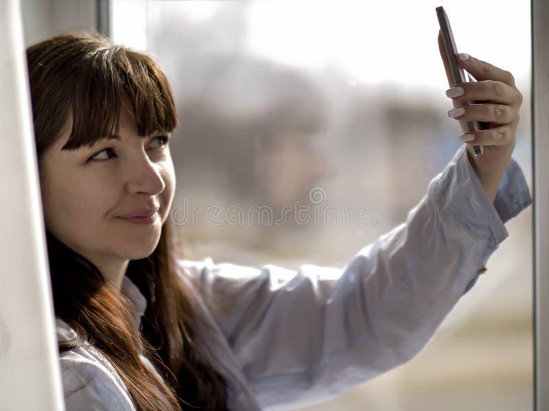La jeune fille de sourire de brune dans une chemise bleue fait le selfie par la fenêtre image stock