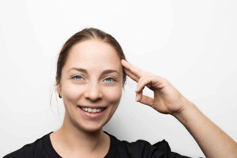 La jeune fille de sourire heureuse tenant la main avec des doigts s'approchent de la tête et de regarder l'appareil-photo, soluti photo stock