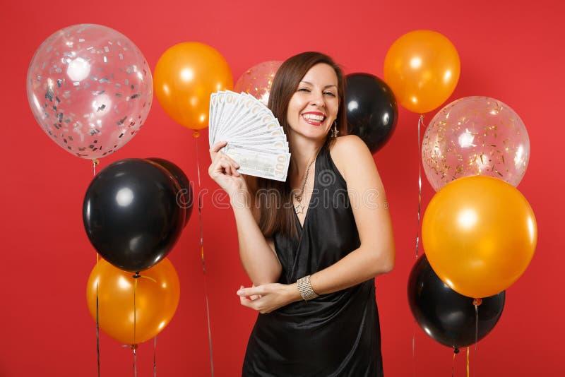 La jeune fille de sourire joyeuse dans la robe noire célébrant tenant un bon nombre de paquet de dollars encaissent l'argent sur  photographie stock libre de droits