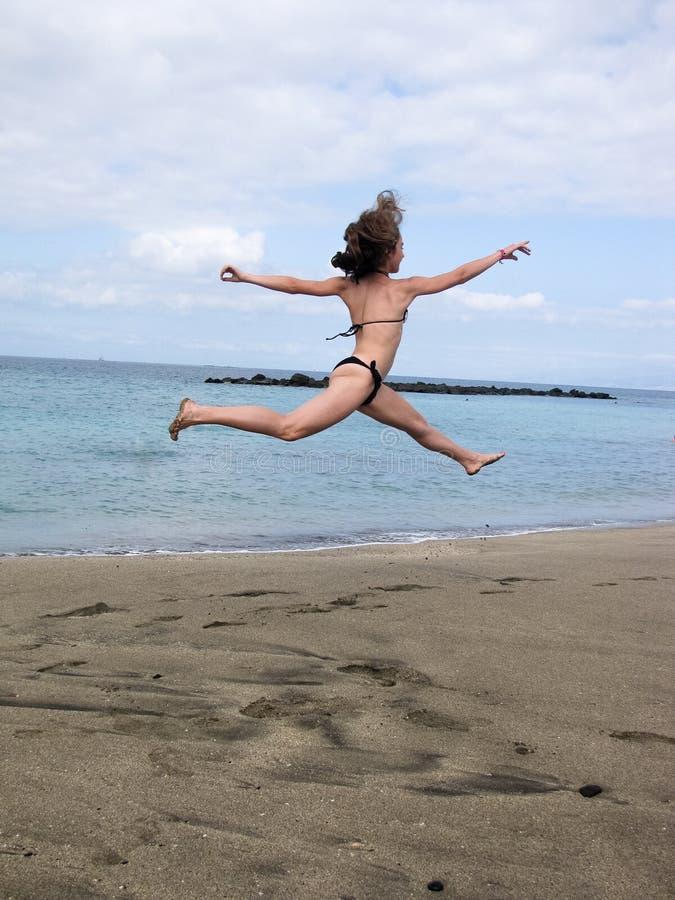 La jeune fille de sport saute haut près de l'océan d'Athlantic images libres de droits