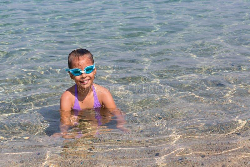 La jeune fille de touristes en verres de sports de natation flotte en mer Égée sur la côte de la péninsule de Sithonia photographie stock libre de droits