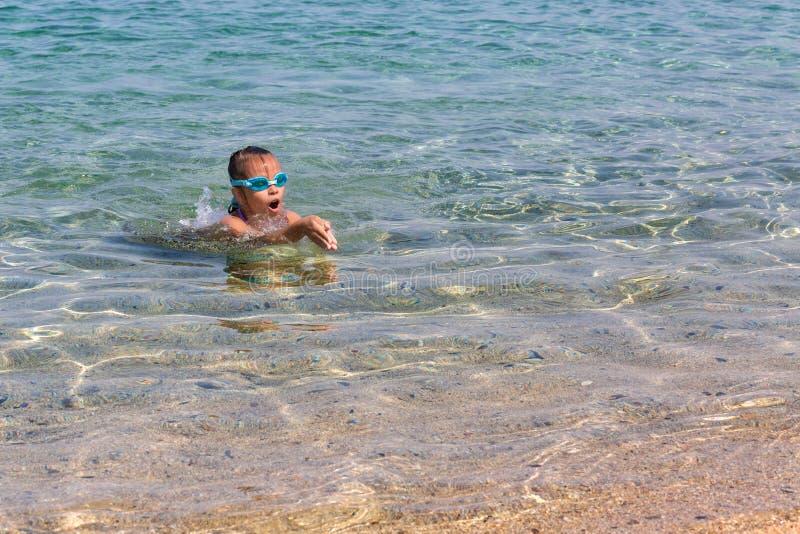 La jeune fille de touristes en verres de sports de natation flotte en mer Égée sur la côte de la péninsule de Sithonia image stock