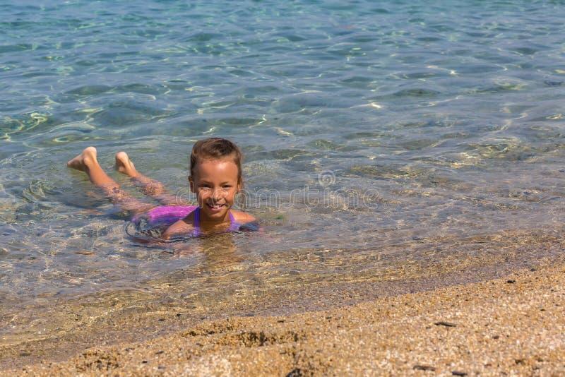 La jeune fille de touristes nage en mer Égée sur la côte de la péninsule de Sithonia photographie stock