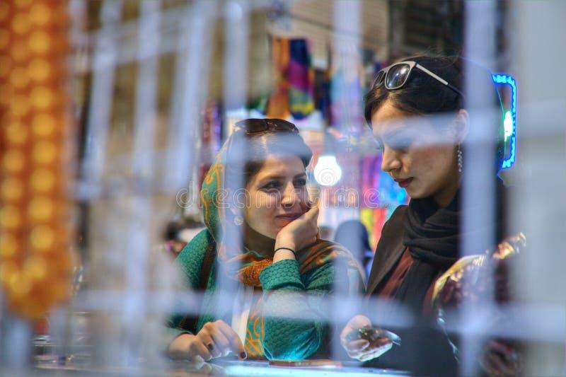 La jeune fille deux iranienne parlent dans le magasin à l'intérieur du bazar photos stock
