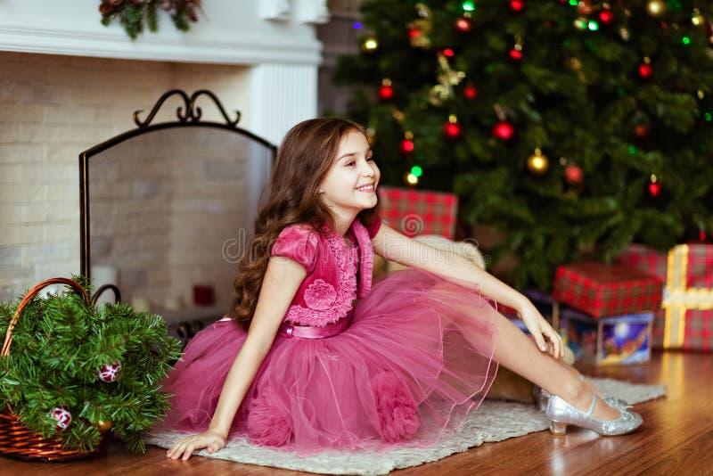 La jeune fille douce dans une robe rose sourit et s'assied près du firepl photos libres de droits