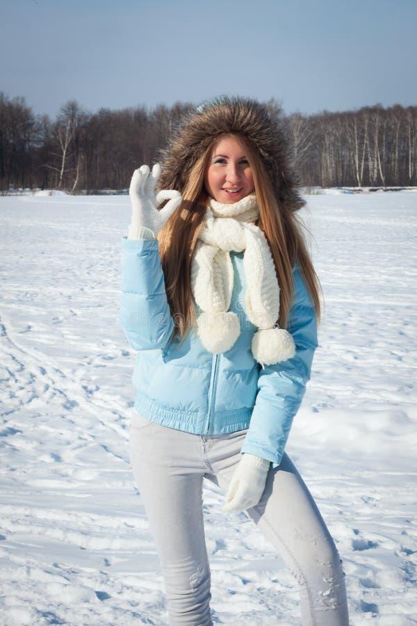 La jeune fille en parc par temps froid d'hiver montre un geste images libres de droits