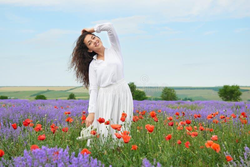 La jeune fille est dans le domaine de lavande, beau paysage d'été avec des fleurs photographie stock
