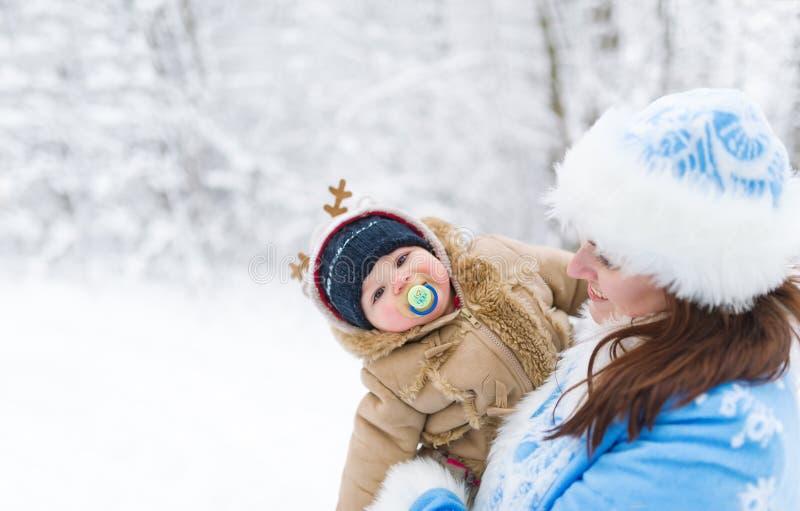 La jeune fille et le bébé garçon de neige embrassant en hiver se garent parmi des branches d'arbres photo libre de droits