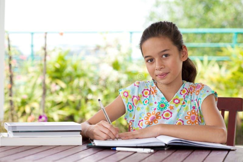 La jeune fille faisant son travail dans une maison environmen photo libre de droits