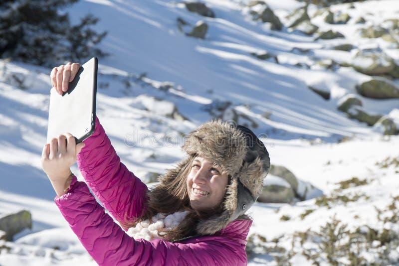 La jeune fille fait des photos de selfie avec un comprimé en hiver images stock