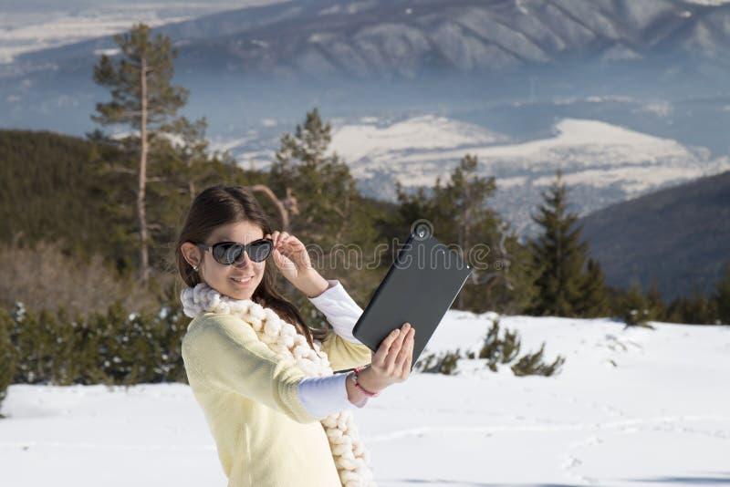 La jeune fille fait des photos de selfie avec un comprimé en hiver photos stock