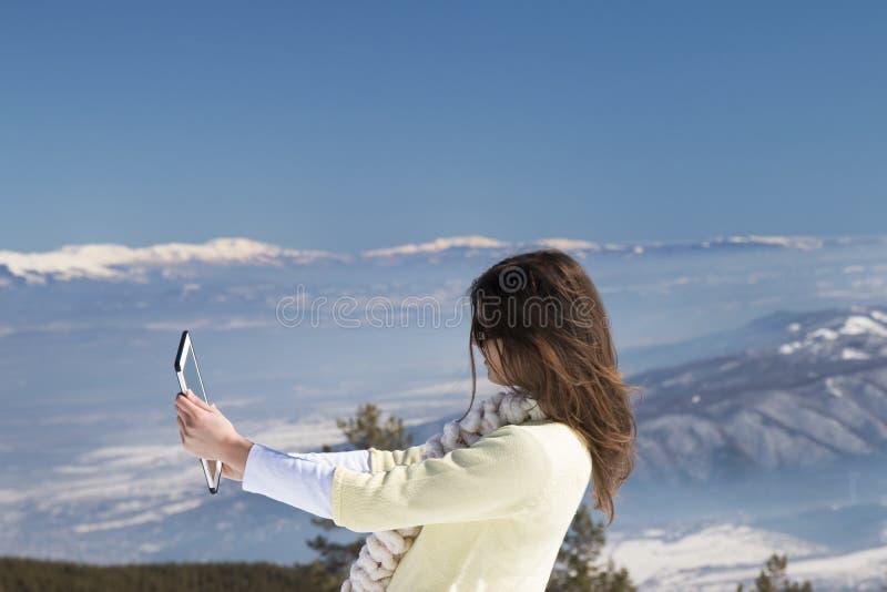 La jeune fille fait des photos de selfie avec un comprimé en hiver image stock