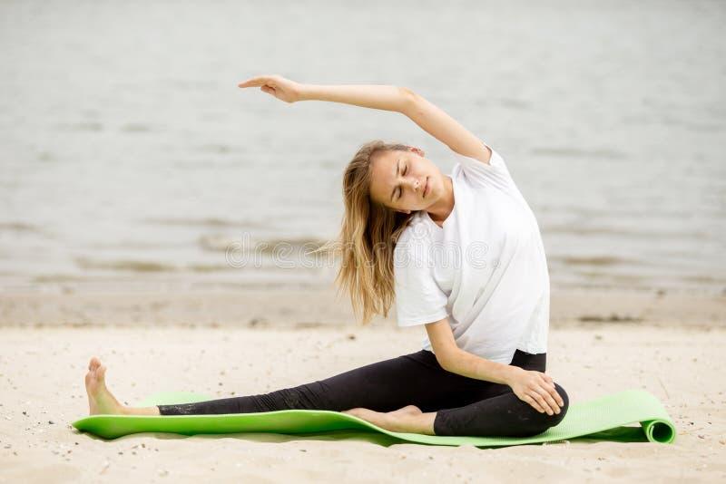 La jeune fille fait l'?tirage sur le tapis de yoga sur la plage sablonneuse un jour chaud images stock