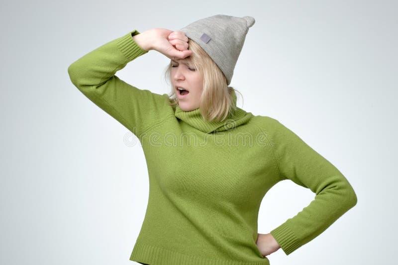 La jeune fille fatiguée mignonne utilisant le chandail vert et le chapeau, baîllant avec ses yeux s'est fermée photographie stock