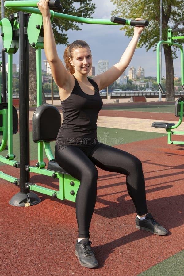 La jeune fille a la formation et faire l'extérieur d'exercice sur des simulateurs de rue Sport, forme physique, concept de s?ance images stock