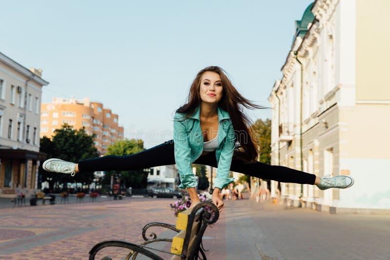 La jeune fille heureuse, ayant l'amusement, sauts et a l'amusement sur la rue lifestyle photos libres de droits