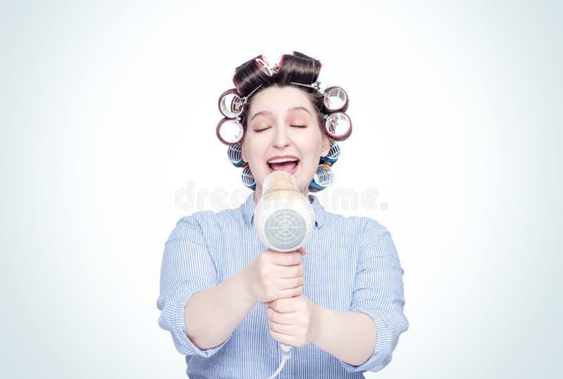 La jeune fille heureuse dans des bigoudis de cheveux chante dans le hairdryer comme un microphone Front View images stock