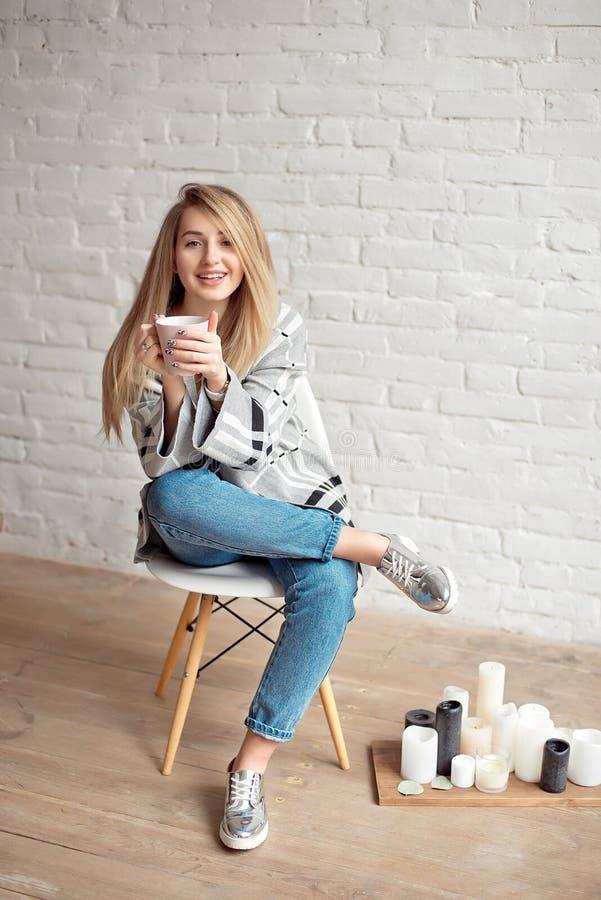 La jeune fille heureuse enveloppée dans une couverture chaude semble heureuse tenant la tasse de thé à l'intérieur image libre de droits