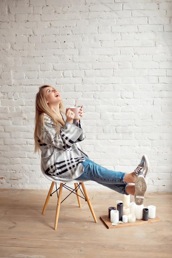 La jeune fille heureuse enveloppée dans une couverture chaude semble heureuse tenant la tasse de thé à l'intérieur photos stock