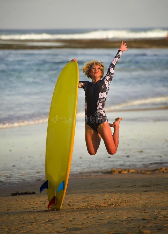 La jeune fille heureuse et attirante de surfer sautant haut dans le ciel tenant le panneau de ressac avant de surfer à la belle p image libre de droits